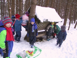 Děti nosí v zimě potravu zvířatům do lesního krmelce